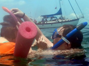 Kristi helps her mom, Patricia, on her first snorkel while Jim watches from the Namaste'.