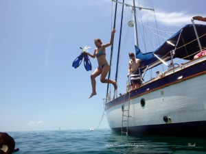 Snorkeler jumping from the deck of a sailboat